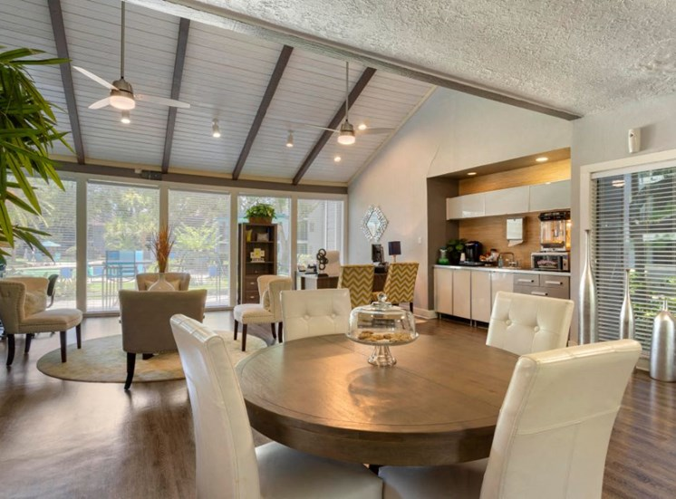 Clubhouse interior with hardwood style flooring, round table, white walls, and large windows