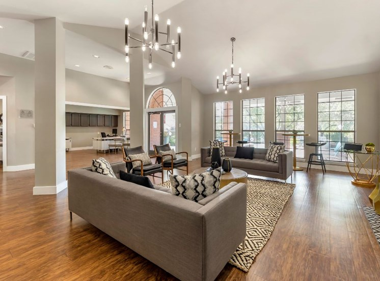 Clubhouse interior with with modern lighting, hardwood floors, and gray couches