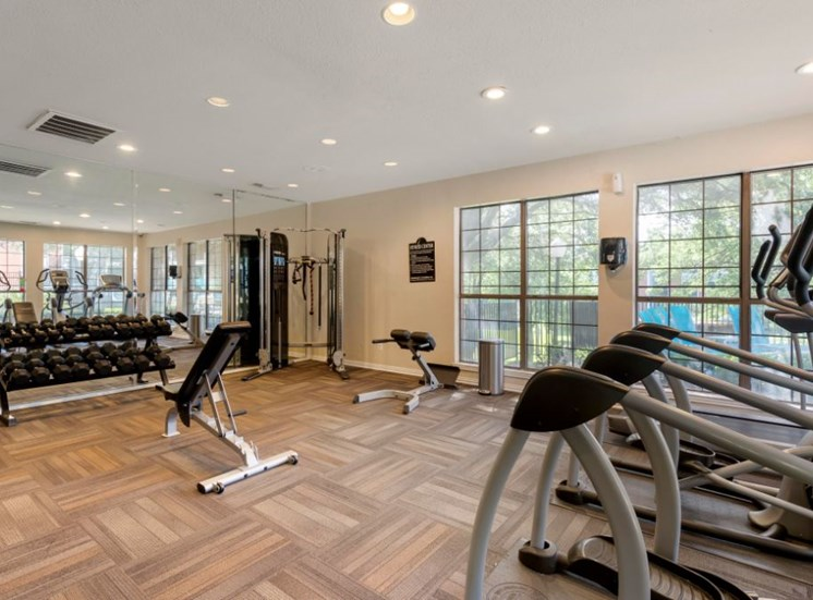 Fitness center with a window and view of the pool and free weights and a treadmill