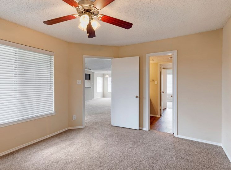 Carpeted bedroom with ceiling fan and en suite bathroom