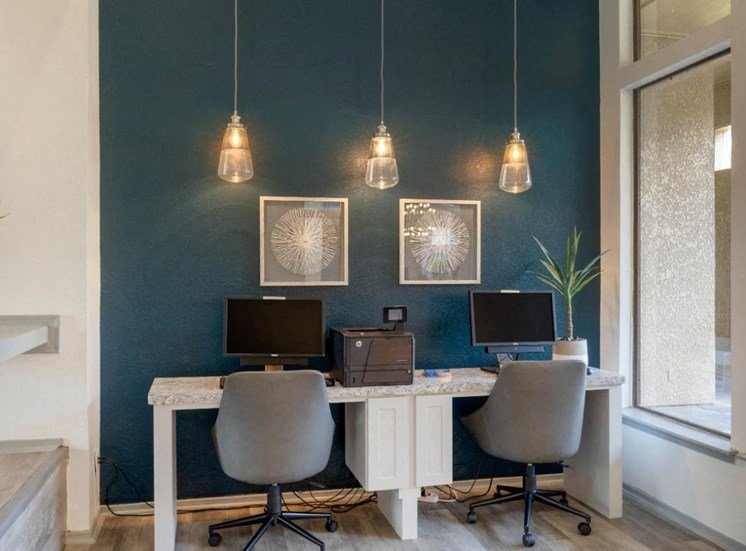 Computer Lab with teal accent wall, 3 lights hanging down, two framed photos, and two computers