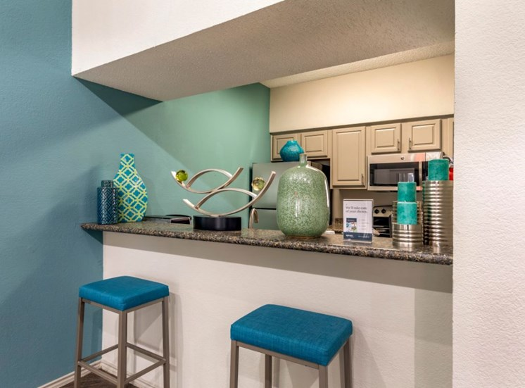 Clubhouse kitchen with teal bar stools, teal accent wall, with decorations on the bar