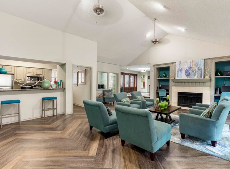 Clubhouse interior with hardwood style flooring, teal accent furniture, arched ceilings, and bar stool seating