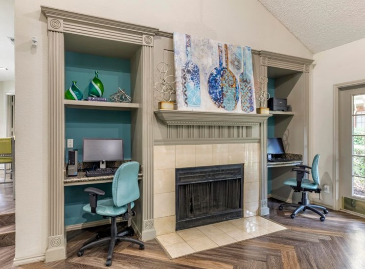Clubhouse interior and business center with teal accent wall and brick fireplace