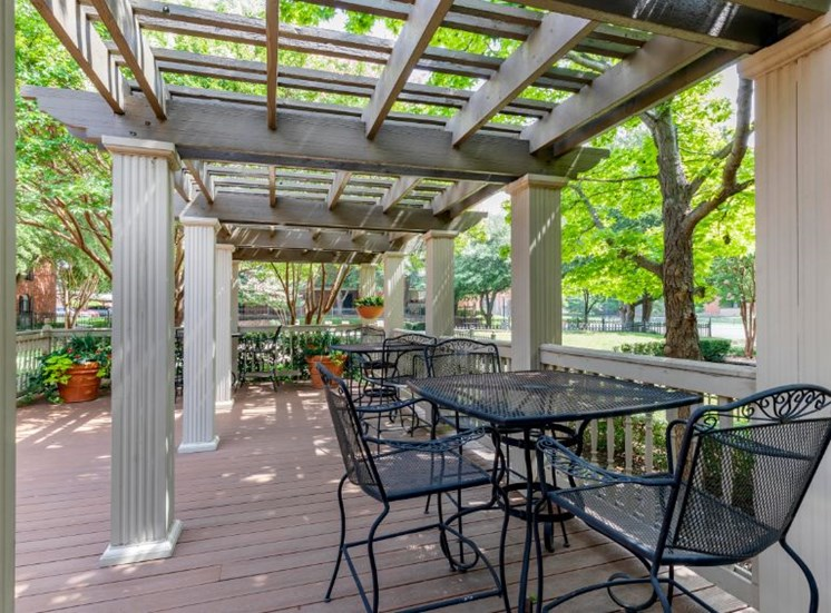 Outdoor seating with chairs, tables, under a pergola