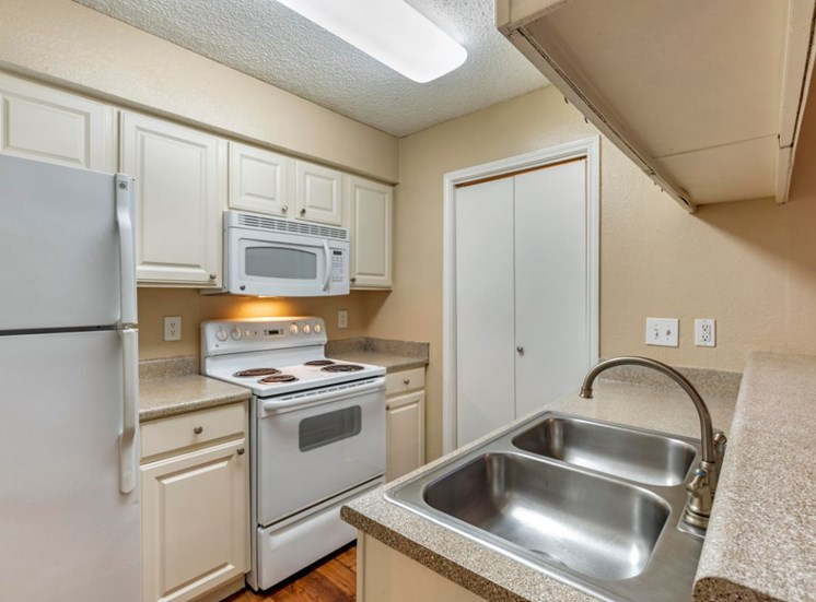 Fully equipped kitchen with double basin sink, brushed nickle appliances, and a pantry with white doors