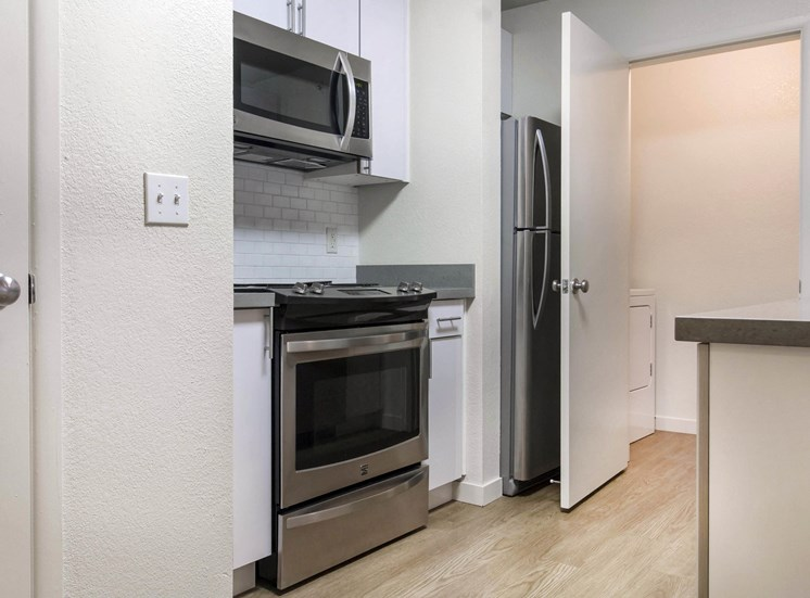 Kitchen with White Cabinets and Stainless Steel Appliances and Utility Closet with Washer and Dryer