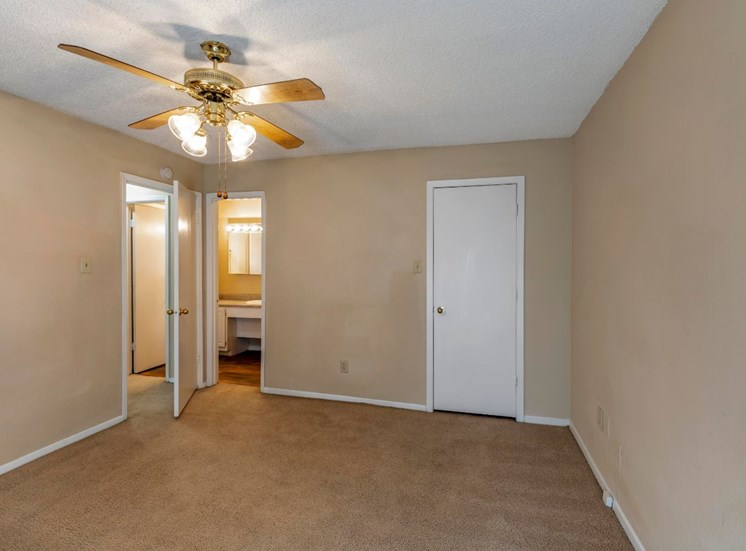 Bedroom with ceiling fan, closet, and wall to wall carpet