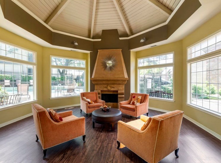 Clubhouse interior with arched ceilings, orange accent chairs, green accent walls, and large windows