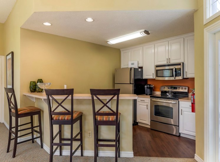 Clubhouse interior with fully equipped kitchen, white cabinets, and hardwood style flooring