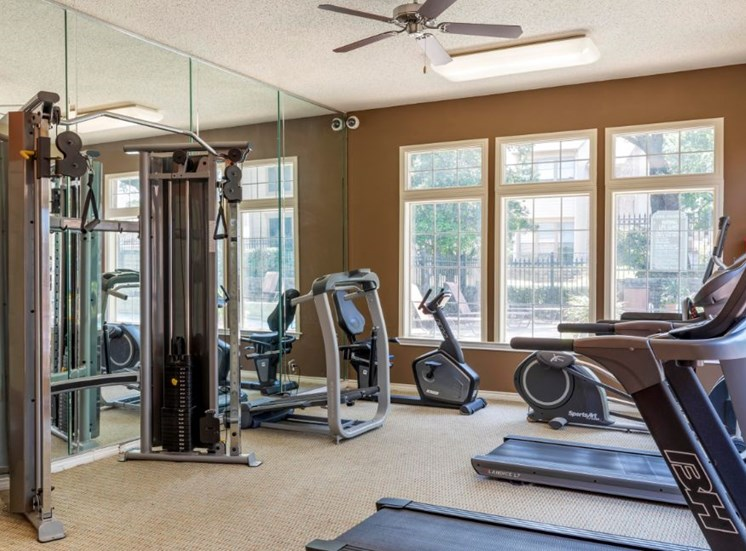 Fitness center with treadmill, wall to wall mirror, and large windows