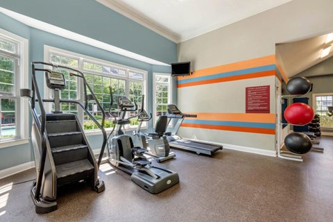 Fitness Center with Exercise Equipment  Against Blue Accent Wall with Windows