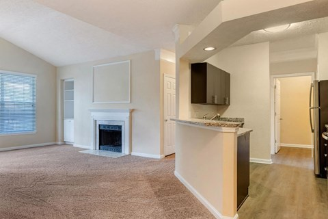 Carpeted Living Room with Fireplace Next to Kitchen with Breakfast Bar