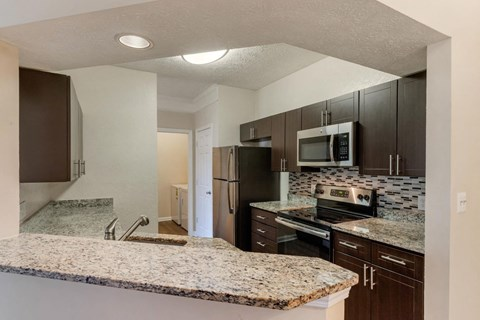 Kitchen with Breakfast Bar Granite Counters Brown Cabinets and Stainless Steel Appliances