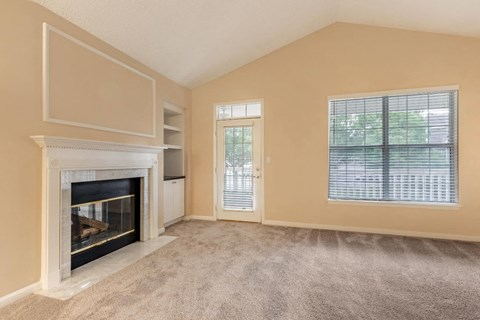 Spacious Carpeted Living Room with Fireplace and Built in Shelving