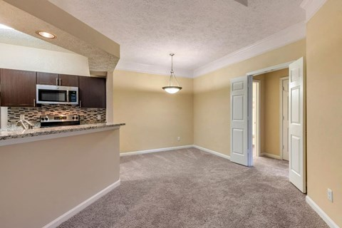 Carpeted Dining Room Next to Kitchen with Breakfast Bar