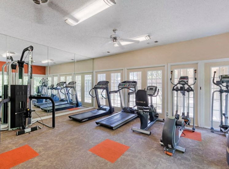 Indoor fitness center with orange and gray accent colors,  treadmills, spinning stations, and windows along the wall