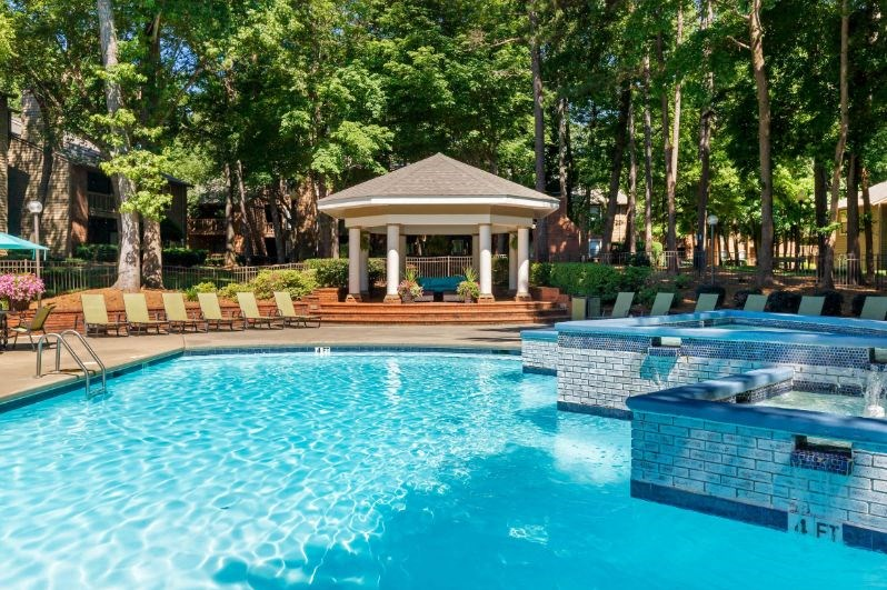 Swimming Pool with Waterfall and Gazebo Next to Lounge Chair