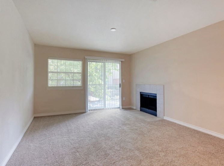 Living room with wall to wall carpet, fireplace, windows, and a sliding patio door,