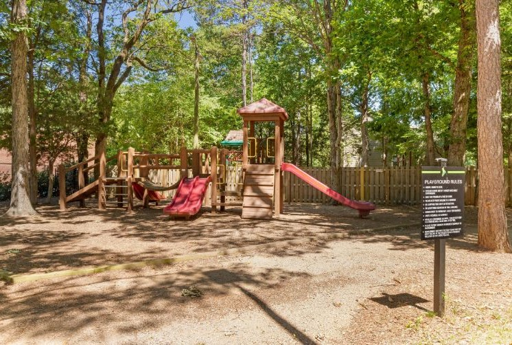 Playground Shaded by Tall Trees in Front of Wooden Fence