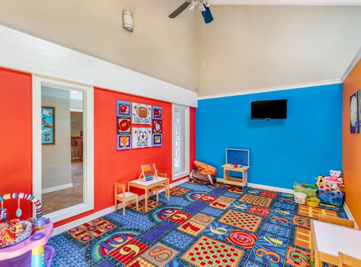 Children's Play Area with toys, a children's desk, and a television mounted on the wall