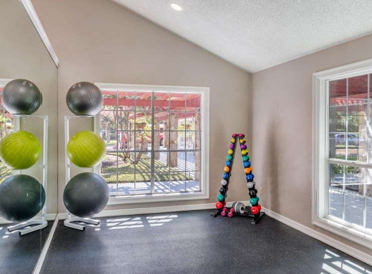 Fitness center with free weights, mirrored wall, and large windows