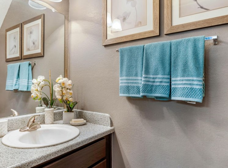 Bathroom with three blue towels hanging on a towel holder, framed photos, and decorations