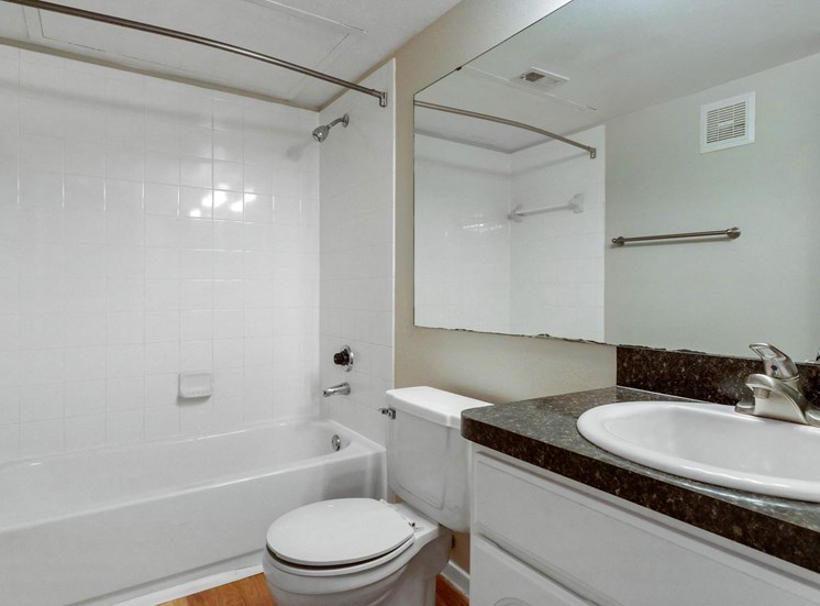 Bathroom with White Cabinets Black Counters and White Bathtub and Shower