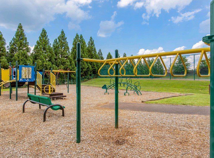 Playground with Green and Yellow Accents on Mulch with Benches with Treeline in the Background