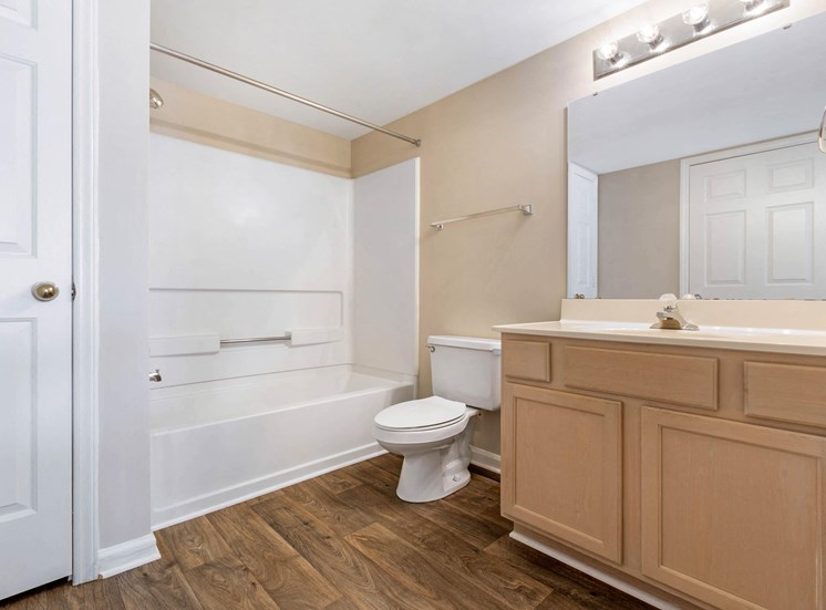 Bathroom with Blonde Cabinets White Counters and White Bathtub and Shower