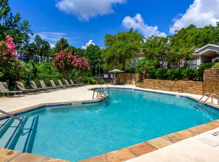 Fenced in Pool with Stone Retaining Wall Sun Deck and Lounge Chairs with Treeline and Office Exterior in the Background