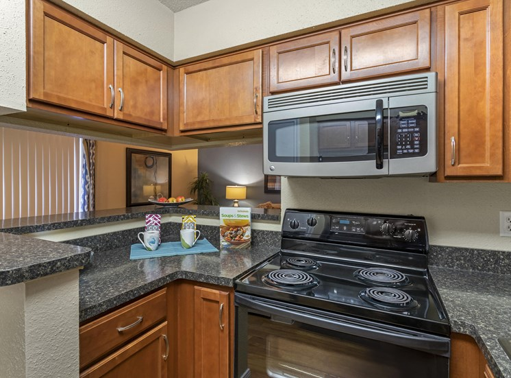 Fully Equipped Model Kitchen with Brown Cabinets and Black Counters