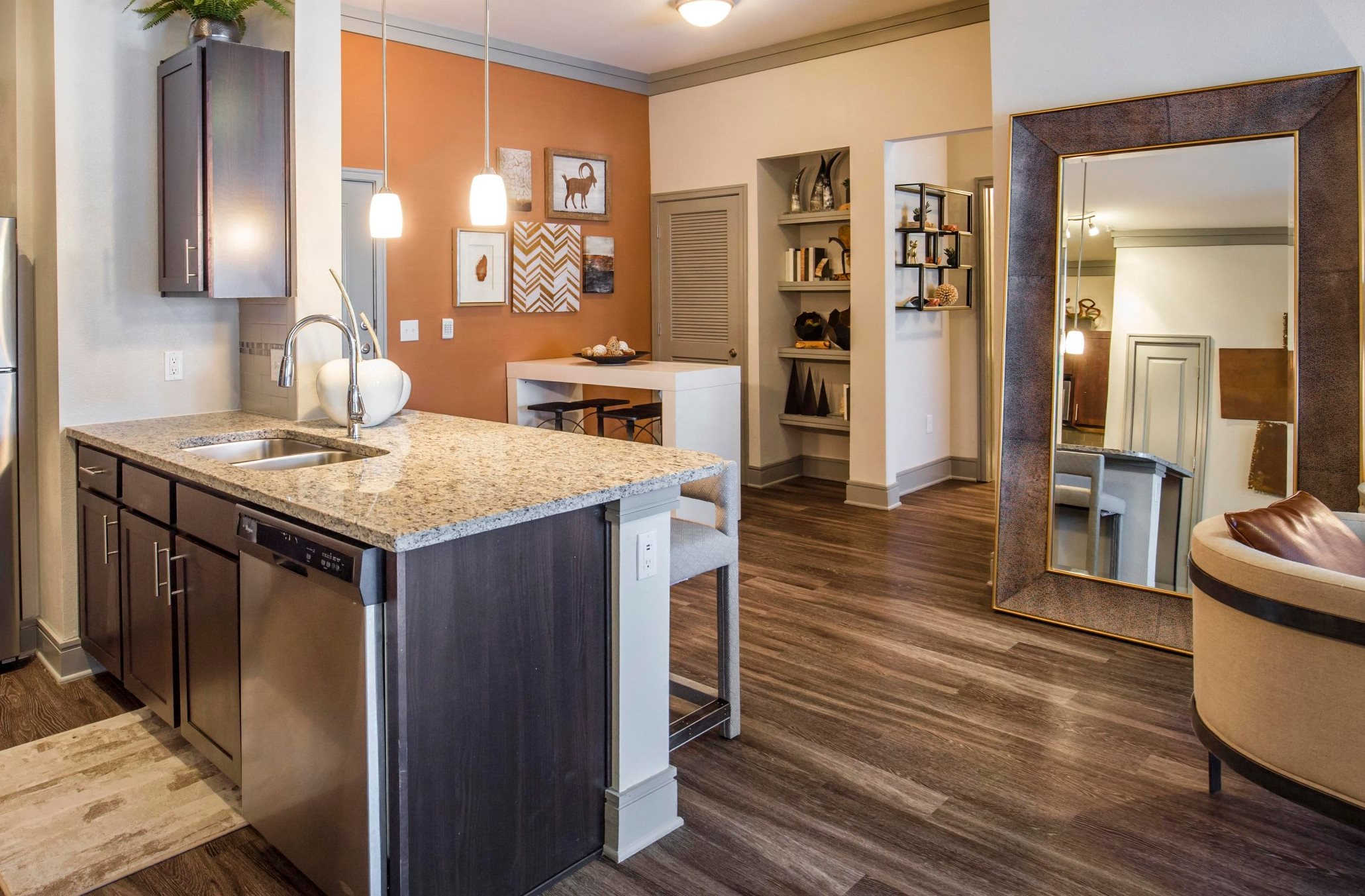 Clubhouse kitchen interior with hardwood style floor, espresso cabinets, and orange accent wall