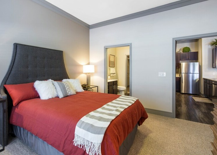 Bedroom with wall to wall carpet and a bed with red linens