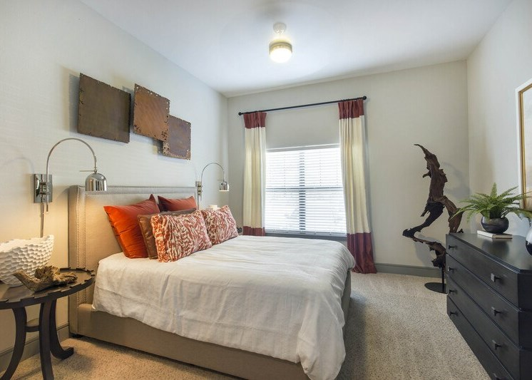 Bedroom with wall to wall carpet and a bed with white linens