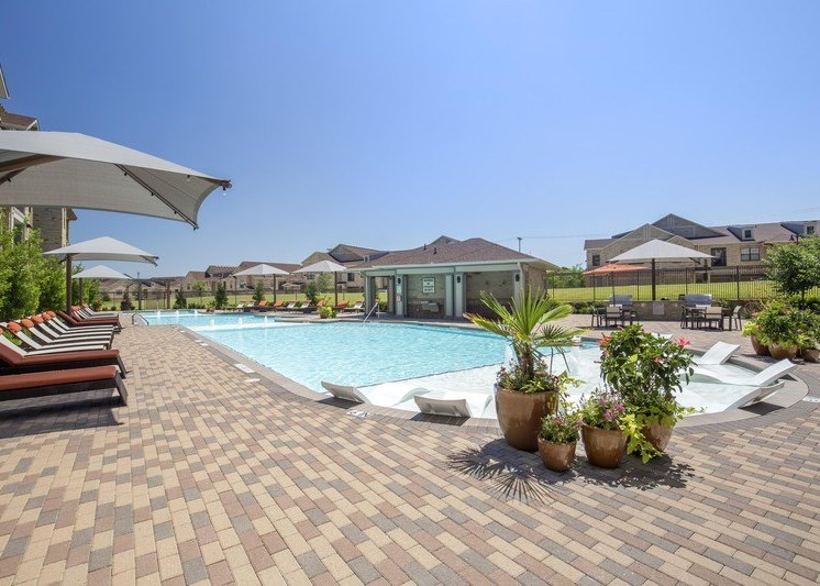 Resort style swimming pool with fountains and pool lounge chairs