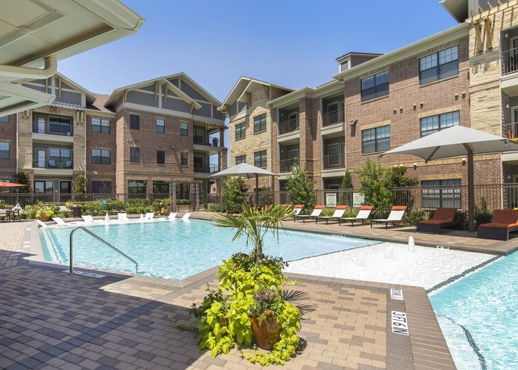 Swimming pool with lush green landscaping, pool chairs, and apartment building exterior in the background