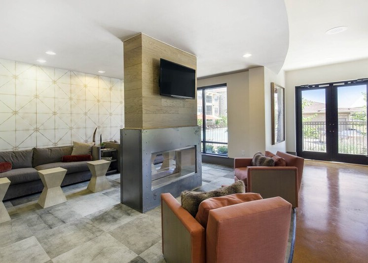 Clubhouse interior with two accent chairs and a fireplace in the center of the room
