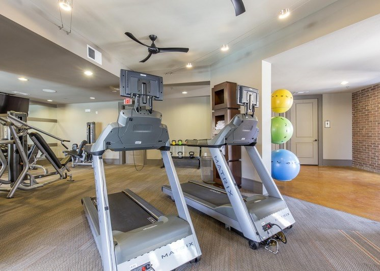 Two treadmills with a ceiling fan and workout medicine balls in the background