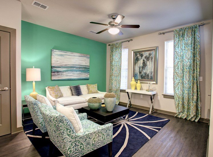 Living room with sofa and arm chairs with blue rug and a ceiling fan