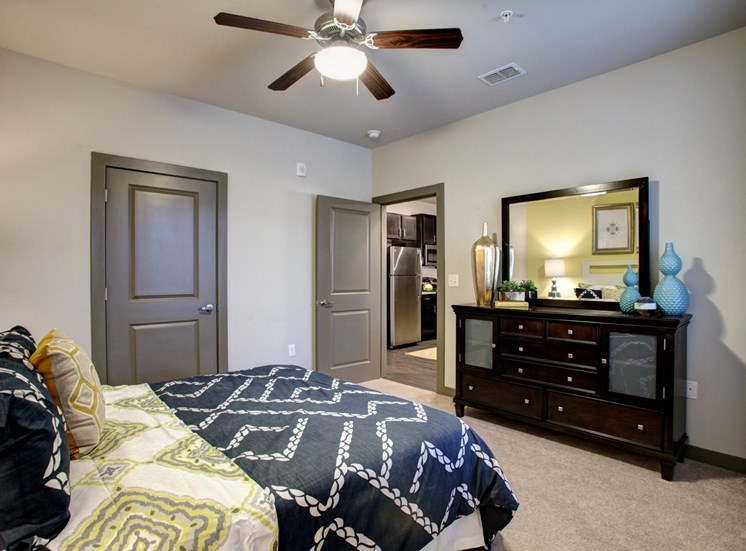 Bedroom with queen size bed . Dresser with a lamp  and mirror. ceiling fan