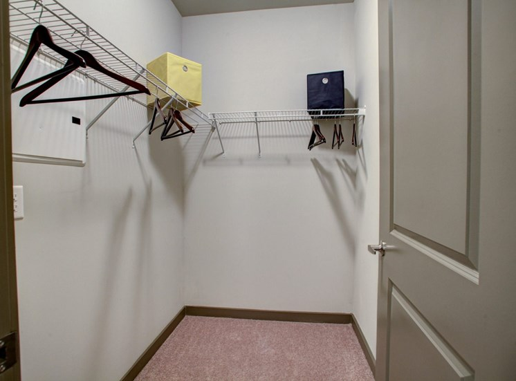 Closet with wire shelves and hangers on them. The shelves have baskets.