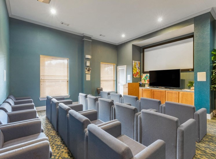 Clubhouse Theater Room with gray chairs, blue walls, and large screen