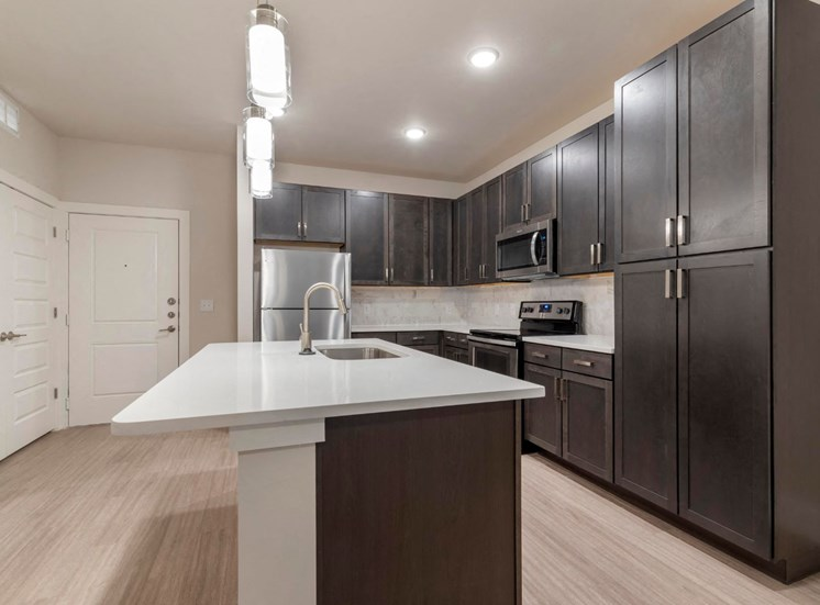 Fully Equipped Kitchen with Island Dark Brown Cabinets White Counters and Stainless Steel Appliances