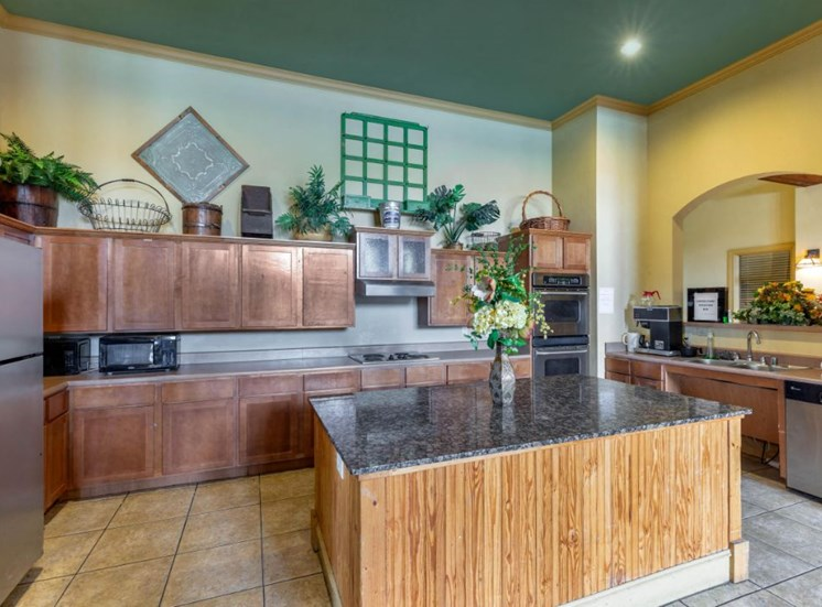 Clubhouse kitchen with island, large counter space, and green and yellow walls