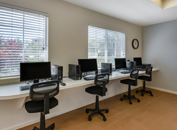 Clubhouse business center with computers, chairs, desk, and large windows for natural lighting