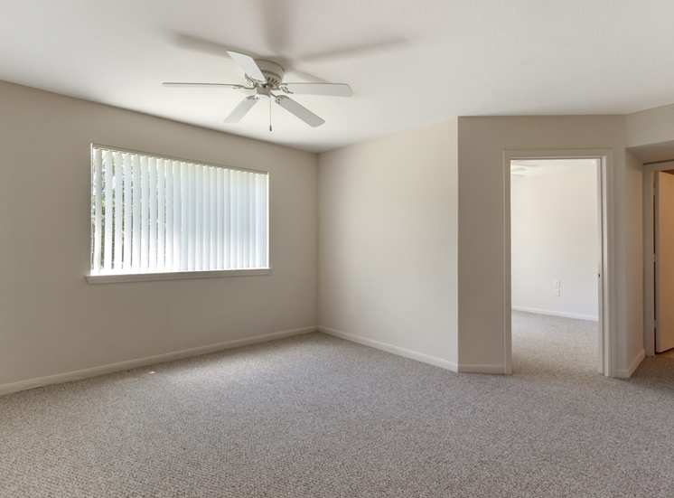 Living room with carpet flooring, multi speed ceiling fan, and large window for natural lighting