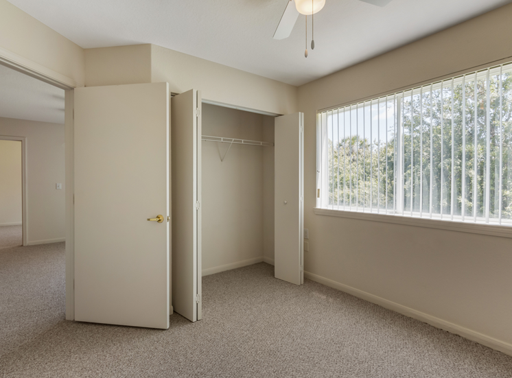 Bedroom with carpet flooring, large reach-in closet, multi speed ceiling fan, and large window for natural lighting