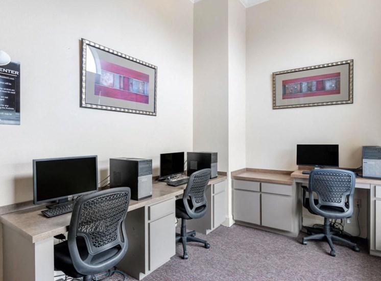 Business Center with computer lab, three chairs, framed photos on the walls, and tan and cream desks