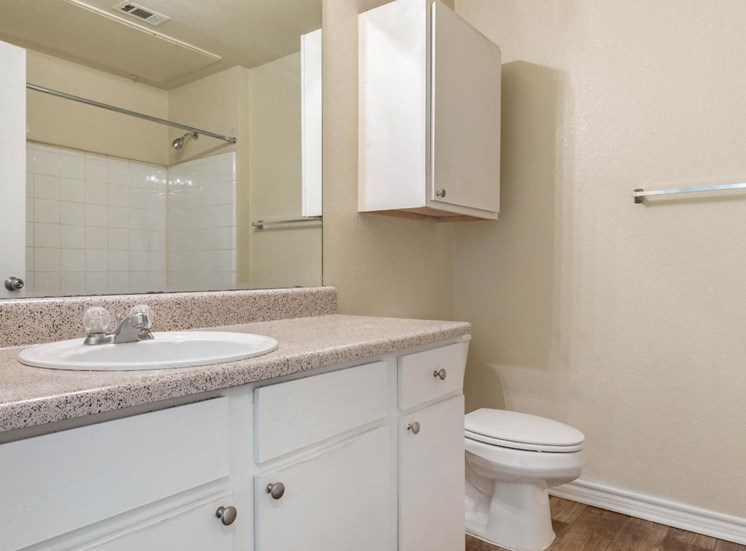 Bathroom with white cabinets and extra storage above the toilet